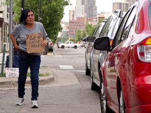 Little Runaway flies a sign on Santa Fe Drive July 21, hoping to get money for food and alcohol.  Photo by Melanie J. Rice • mrice20@msudenver.edu